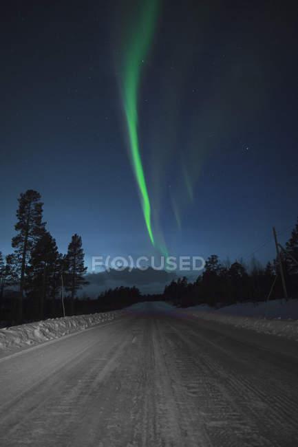 Idyllic view of Aurora Borealis over snow covered road at night, Kiruna, Sweden — Stock Photo