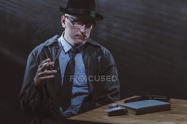 Joven sentado en la mesa mientras fuma cigarrillo contra la pared negra - foto de stock