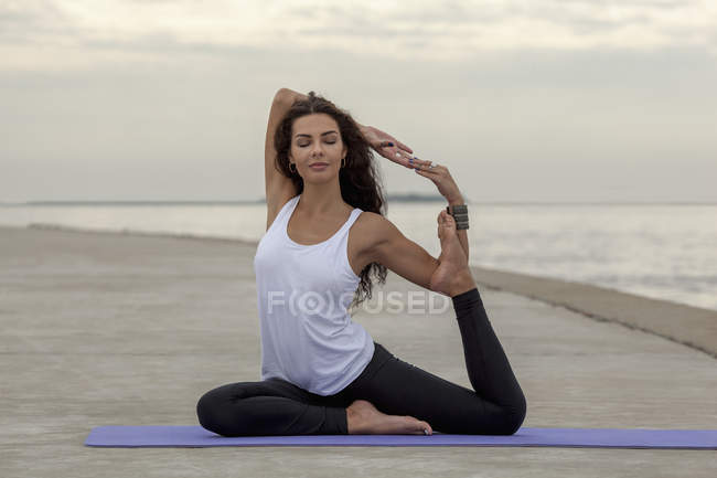 Beautiful woman practicing yoga in mermaid pose at beach — Stock Photo