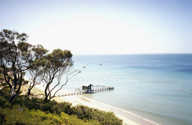 Idyllic beach with pier on summer day — Stock Photo