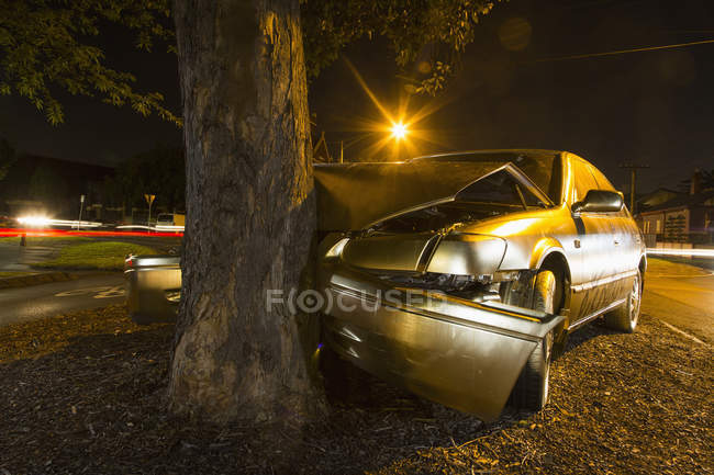 Close up view of car crashed on tree trunk at night street — Stock Photo