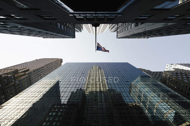 Directly below view of American Flag amidst modern office skyscrapers — Stock Photo