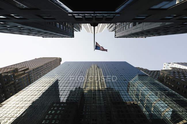 Directement en dessous de la vue du drapeau américain au milieu des gratte-ciel de bureau modernes — Photo de stock