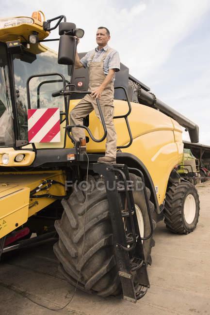 Homem maduro em pé em máquinas agrícolas na fazenda — Fotografia de Stock
