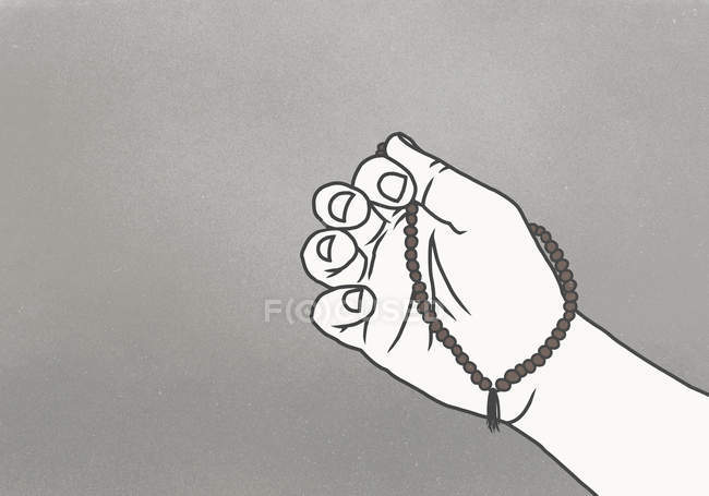 Cropped image of hand holding prayer beads against gray background — Stock Photo