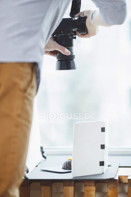 Cropped image of photographer photographing food on table against window — Stock Photo