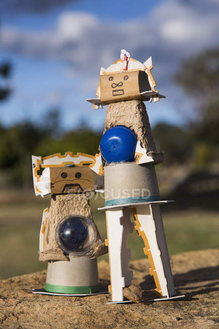 Cardboard characters on stone against sky — Stock Photo