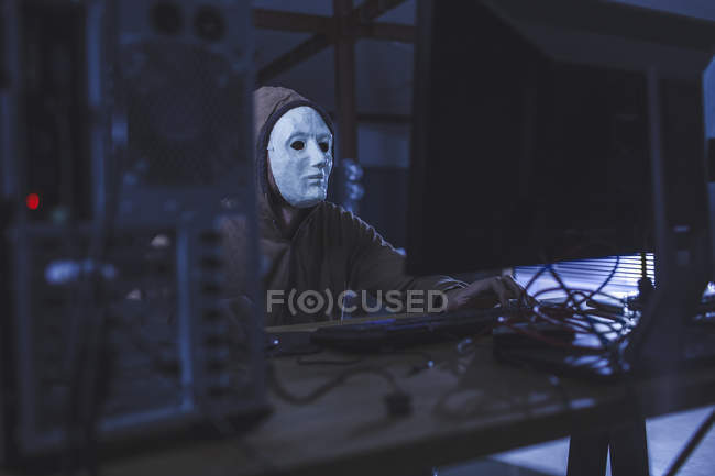 Man wearing mask and hood browsing computer — Stock Photo