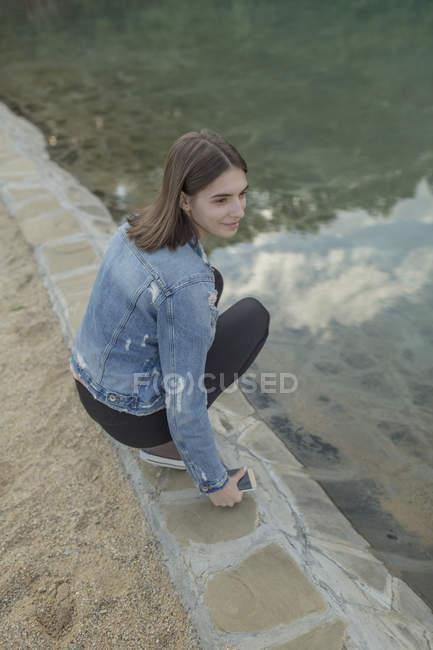 Donna sorridente accovacciata sul muro di contenimento al lago nel parco — Foto stock
