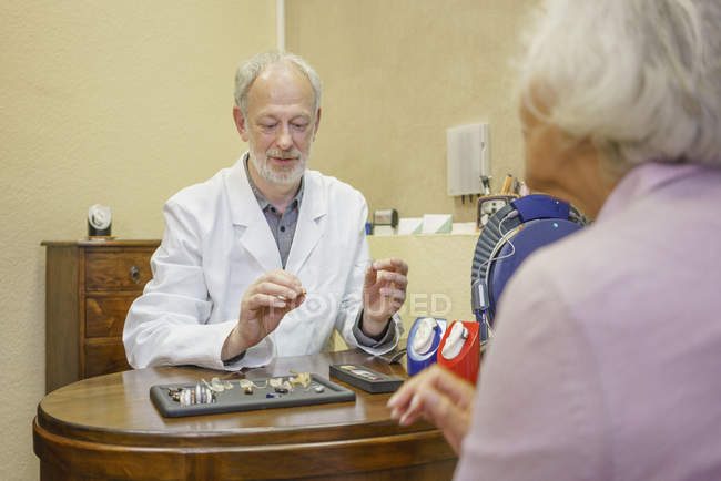 Doctor with hearing aids explaining to senior woman at clinic — Stock Photo