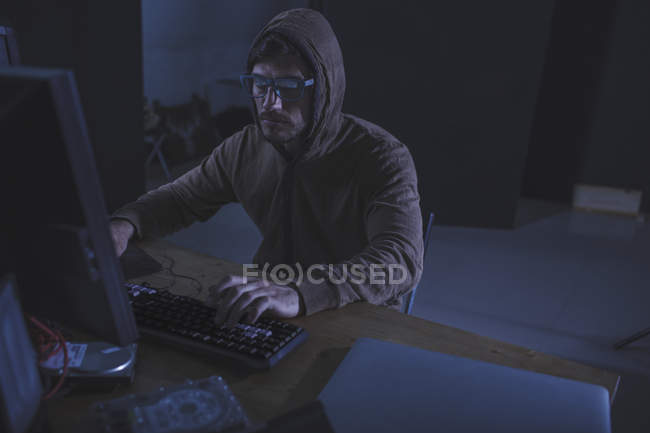 Serious computer hacker wearing hooded shirt using desktop computer at table in abandoned room — Stock Photo