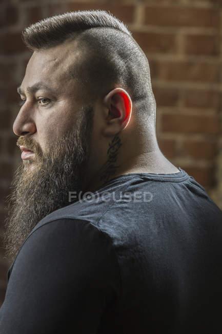 Close-up de cabeleireiro masculino com barba olhando para longe na barbearia — Fotografia de Stock