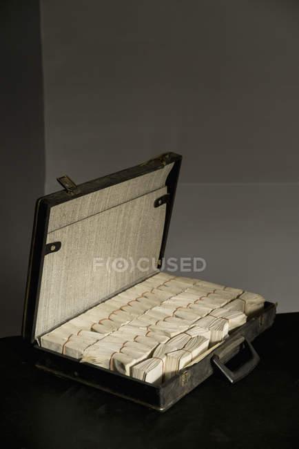 Manojo de sobres dispuestos en maletín abierto en la mesa - foto de stock
