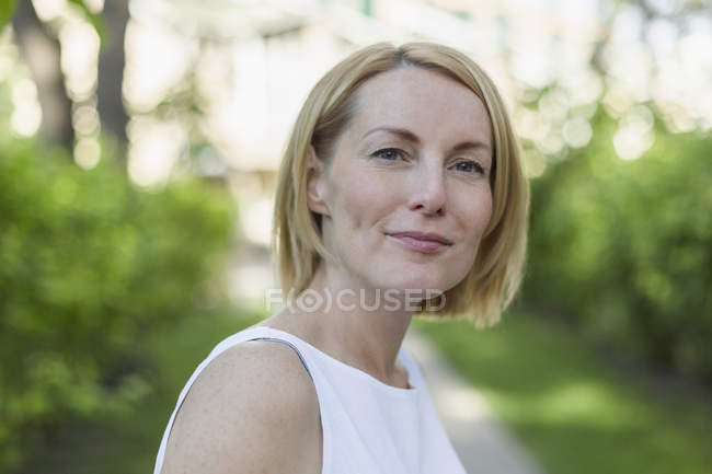 Portrait of confident smiling mature woman with short blond hair in park — Stock Photo