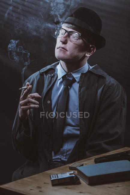 Joven sentado en la mesa con pistola mientras fuma cigarrillo - foto de stock