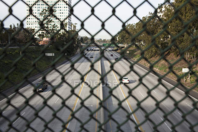 Highway scene seen through chain-link fence — Stock Photo