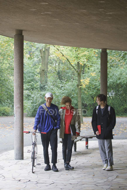 Happy friends talking while walking in gazebo against trees at park — Stock Photo