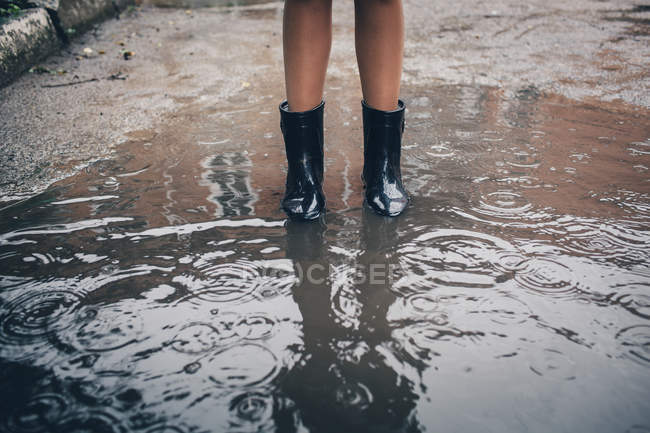 Low section of teenager wearing rubber boot standing in puddle during rain — Stock Photo