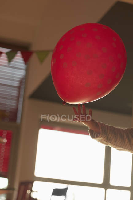 Cropped image of hand playing with red balloon in room at home — Stock Photo