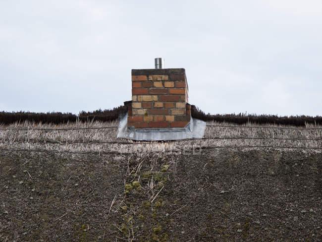 Thatched tetto e camino in mattoni contro il cielo — Foto stock