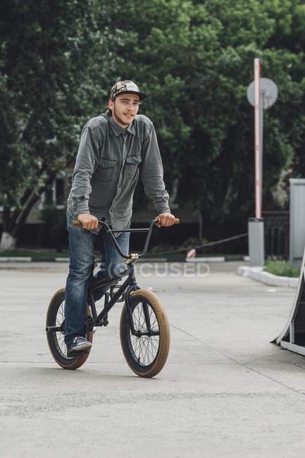 Smiling teenage boy cycling at skateboard park — Stock Photo