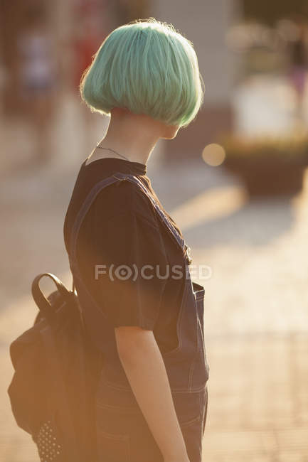 Ragazza adolescente che porta lo zaino mentre si trova in città durante la giornata di sole — Foto stock