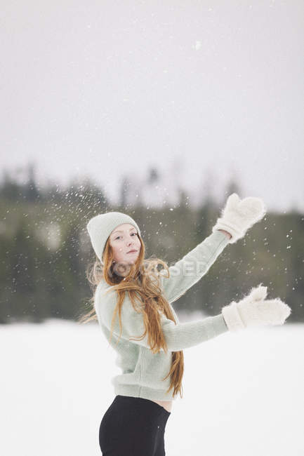 Портрет молодой женщины в теплой одежде, стоящей с поднятыми руками в снежную погоду — стоковое фото