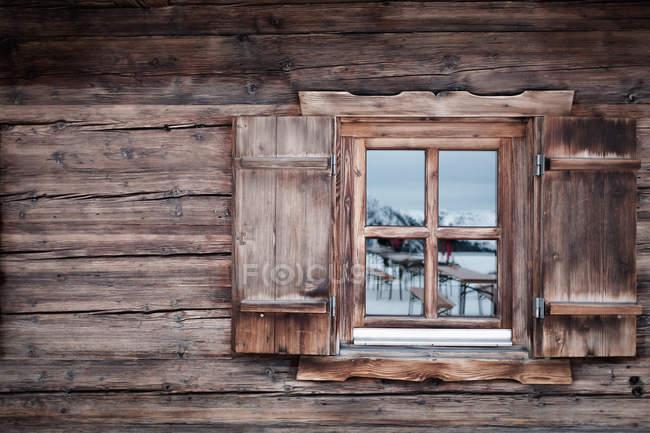 Reflexión sobre la ventana de cristal de la cabaña de madera, Kufstein, Tirol, Austria - foto de stock