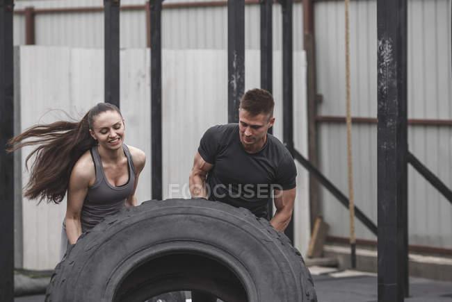 Чоловічий інструктор допоможе спортсменка в гортати tire під час Кроссфіт тренування — стокове фото