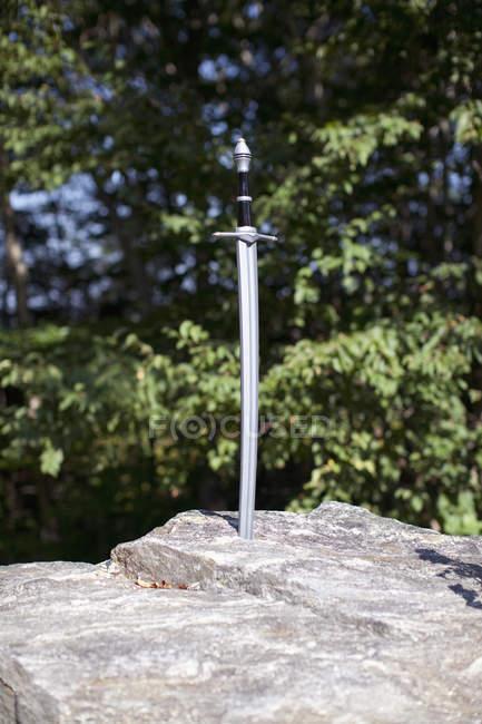 Toy sword stuck in big boulder — Stock Photo