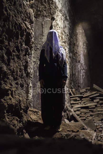 Piena lunghezza di donna con viso oscurato in piedi in grotta — Foto stock
