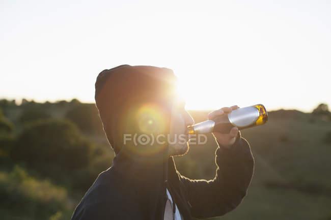 Homem com capuz casaco beber cerveja na natureza em dia ensolarado — Fotografia de Stock