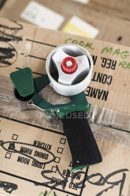 Close up view of tape dispenser on cardboard box — Stock Photo