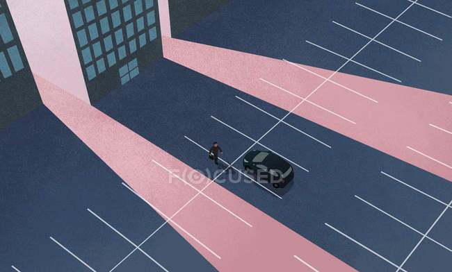 High angle view of man walking towards car at parking lot against building - foto de stock