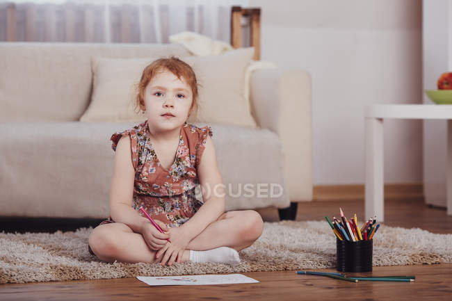 Portrait of smiling girl drawing while sitting on carpet in living room at home — Stock Photo