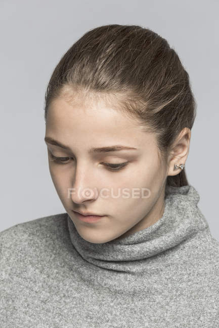 Close-up of teenage girl against gray background — Stock Photo