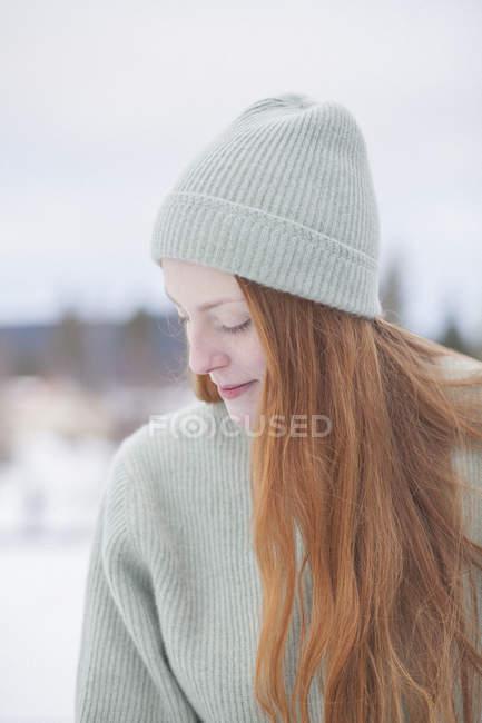 Задумчивая молодая женщина с длинными рыжими волосами в вязаной шляпе и свитере зимой — стоковое фото