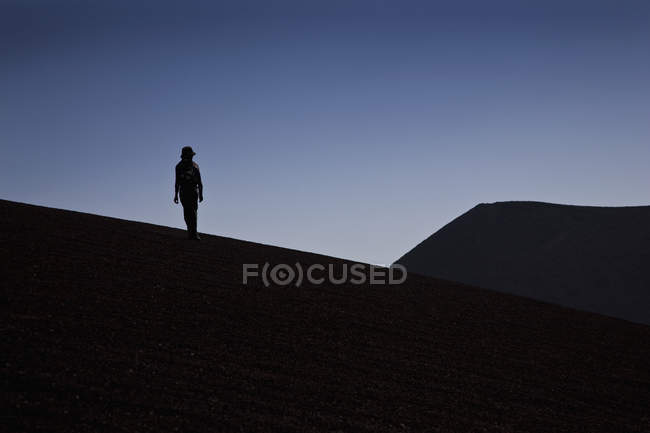Silhouette of a person standing on hill against blue sky — Stock Photo