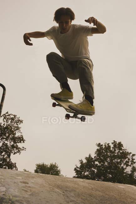 Jeune homme faire truc tout en planche à roulettes dans le parc — Photo de stock