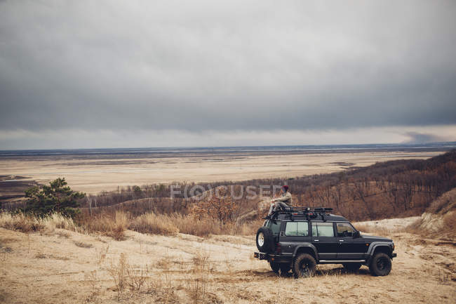 Distant man sitting on top of sports utility vehicle at field against cloudy sky — Stock Photo