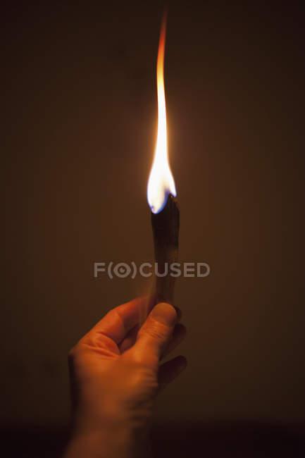 Imagem cortada de mão segurando queimar pau de madeira contra parede — Fotografia de Stock