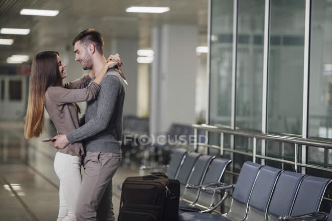 Seitenansicht eines glücklichen jungen Paares, das sich am Flughafen umarmt — Stockfoto