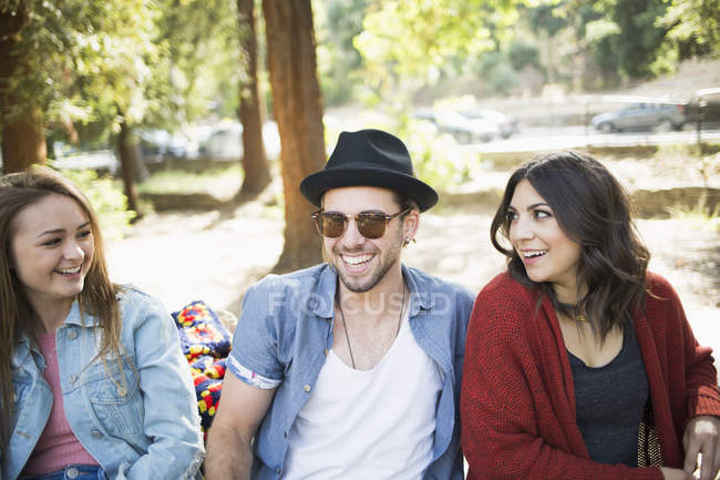 Happy male and female friends sitting on bench in park — Stock Photo