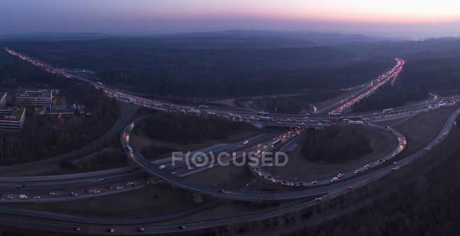 Vue aérienne des routes qui se croisent au milieu du paysage au coucher de soleil crépuscule — Photo de stock