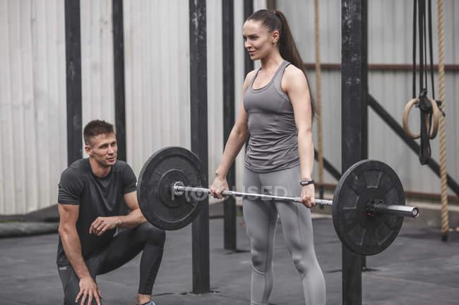 Männliche Lehrer betrachten junge Frau Crossfit Training im Fitnessstudio — Stockfoto