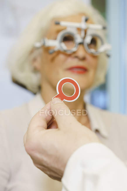 Hand of doctor holding medical equipment while examining patient at clinic — Stock Photo