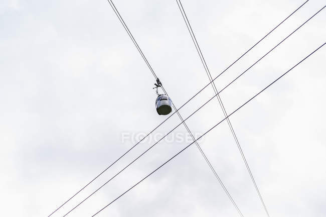 Bottom view to ski lift cabin on cables over clear sky — Stock Photo