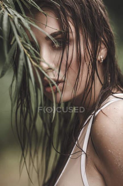 Портрет молодой женщины с мокрыми волосами на заводе — стоковое фото