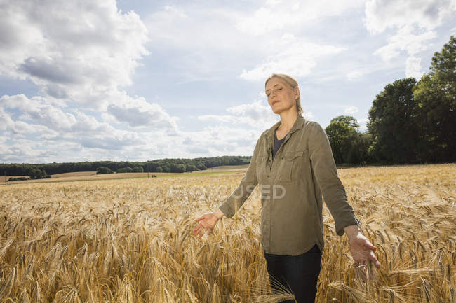 Thoughtful woman standing amidst wheat crop at farm — Stock Photo