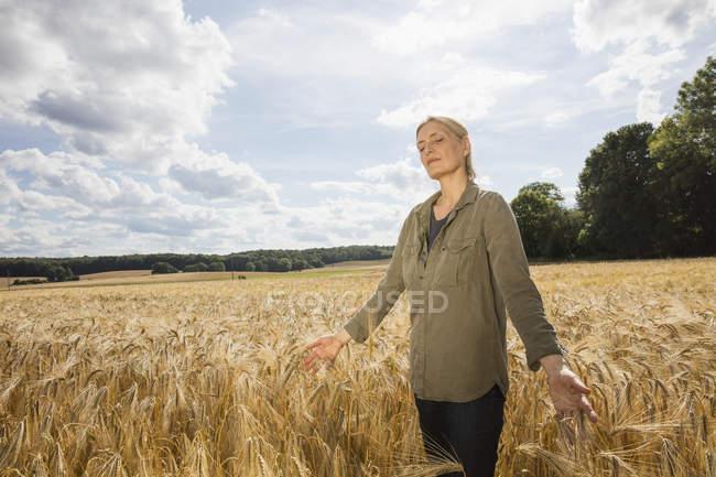 Продуманий жінку, що стоїть посеред пшениці врожаю на фермі — стокове фото